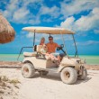 Dad and his two daughters driving golf cart on a tropical beach — Stock Photo #27680589