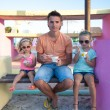 Father with little cute  daughters eating ice-cream outdoor — Stock Photo