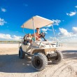 Stock Photo: Dad with his two daughters driving golf cart at tropical beach