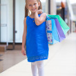 Little fashion girl with packages in large shopping center — Stock Photo #27681803