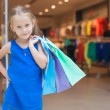 Little fashion girl with packages in a large shopping center — Stock Photo #27681911