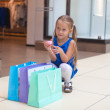 Little fashion girl sits near packages in a large shopping center — Stock Photo #27682213