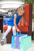 Little fashion girl looking at her purchases — Stock Photo