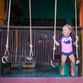 Egzotik bir ülke sokakta bir salıncak üzerinde küçük kız — Stok fotoğraf