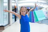 Portrait of little happy girl holding shopping bags at the mall — Stock Photo