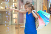 Little girl with packages in a large shopping center — Stock Photo
