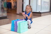 Little fashion girl sits near packages in a large shopping center — Stock Photo