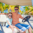 Golf cart with father and his little daughters inside at tropical country — Stock Photo