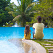 Rear view of a young father and his cute daughter sitting by the swimming pool — Stock Photo