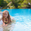Cute little girl in the swimming pool looks at camera — Stock Photo