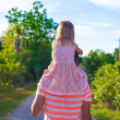 Little girl riding on her dad walking in the garden — Stock Photo