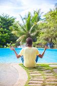 Junger mann sitzt in der lotus-position neben dem schwimmbad — Stockfoto
