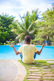 Young man sitting in the lotus position near the swimming pool — Stock Photo