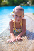 Adorable girl in the swimming pool with flower behind her ear looks at camera — Stock Photo