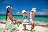 Young mother and two her fashion kids at exotic beach on sunny day — Stock Photo