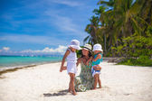Young mother and two her daughters at exotic beach on sunny day — Stock Photo