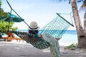 Woman in hat lying in hammock in tree's shadow on a beach — Stock Photo