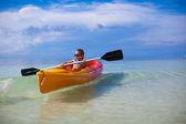 Little cute girl rowing a boat in clear sea — Zdjęcie stockowe