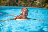 Little cute happy girl swims in the swimming pool — Stock Photo