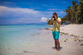 In front of the camera young man with camera in hand on beautiful white sandy beach — Stock Photo
