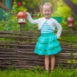 Adorable little girl standing near vintage wooden rural fence and smiling — Stock Photo