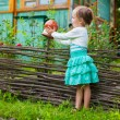 Adorable little girl standing near vintage wooden rural fence — Stock Photo