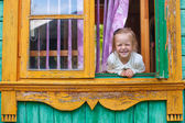 Adorable little girl looks out the window rural house and laughs — Stock Photo