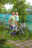 Young father and cute little daughter cycling around the farmhouse — Stock Photo