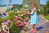 Сute girl in blue dress watering flowers with a hose in her garden — Stock fotografie