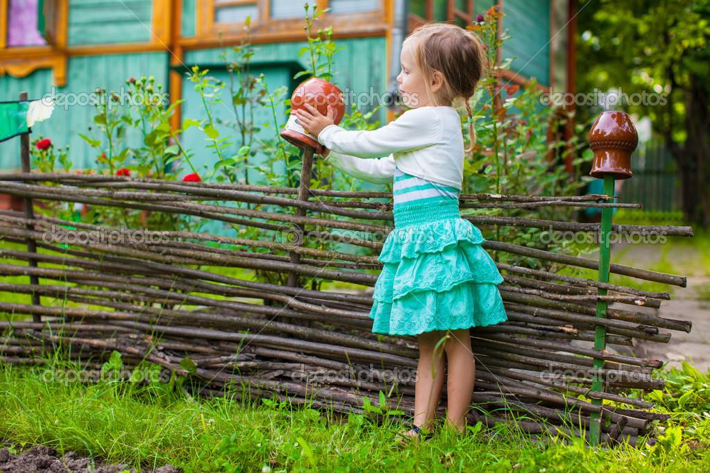 可爱的小女孩站在老式木制农村栅栏附近 - 图库图片