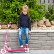 Stock Photo: Little girl riding scooter in her yard