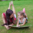 Young mother and her cute daughter reading book and enjoying holiday — Stock Photo