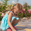Cute small girl drawing on the sidewalk with chalk in the yard — Stock Photo