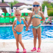 Two cute little sisters standing together near swimming pool — Stock Photo #28651367