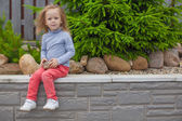 Adorable little girl sitting in the garden in her yard — Stock Photo