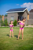 Two little sisters frolicing and splashing in their yard — Stock Photo
