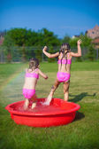 Dvě sestřičky frolicing a stříkající na jejich dvoře v malém bazénu — Stock fotografie