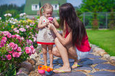 Young mother with her beautiful daughter sniffing flowers in the garden — Stock Photo
