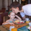 Father kiss his daughter before breakfast in the restaurant — Stock Photo