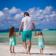 Back view of father and his two little daughters walking by the sea — Stock Photo