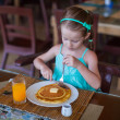 Adorable little girl having breakfast at resort restaurant — Stock Photo