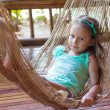 Little cute girl in a hammock on the terrace of her house — Stock Photo