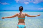 Back view of beautiful girl in swimsuit walking like a bird — Stock Photo