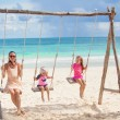 Young mother and her cute daughter swinging on a swing at the beach — Stock Photo #29289759