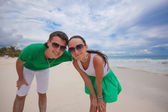 Young couple walking on exotic beach looking at camera — Stock Photo