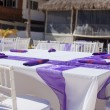 White wedding table decorated with purple bows on sandy beach — Stock Photo