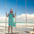 Little cute girl in dress riding a seesaw on the beach — Stock Photo