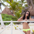 Young sexy womin swimsuit near white fence in exotic resort — Stock Photo #29290265