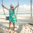 Adorable little girl in a dress and sunglasses on swing on white sandy Caribbean beach — Stock Photo #29290289