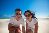 Happy couple looking at camera on exotic white beach — Stock Photo